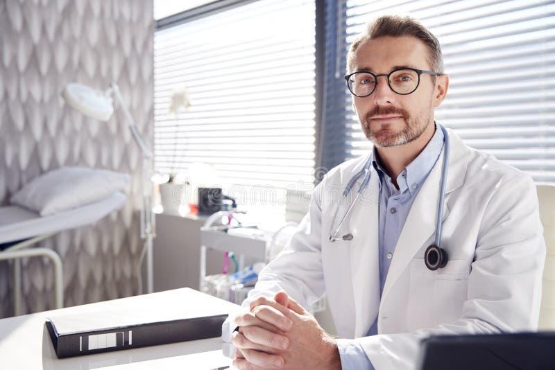 Portrait de docteur masculin de sourire Wearing White Coat avec le stéthoscope se reposant derrière le bureau dans le bureau image stock