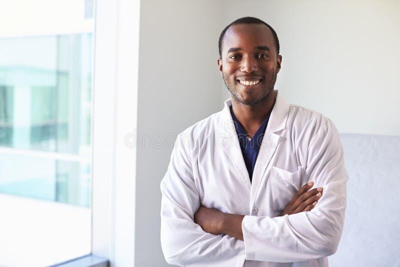 Portrait de docteur masculin Wearing White Coat dans la chambre d'examen photographie stock libre de droits