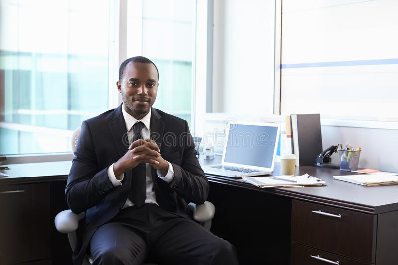 Portrait de docteur Sitting At Desk dans le bureau photos stock