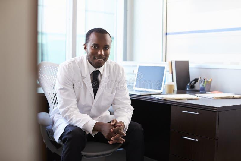 Portrait de docteur Wearing White Coat dans le bureau images stock
