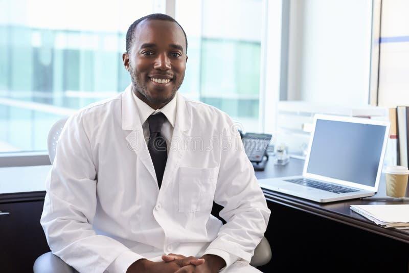 Portrait de docteur Wearing White Coat dans le bureau photographie stock libre de droits
