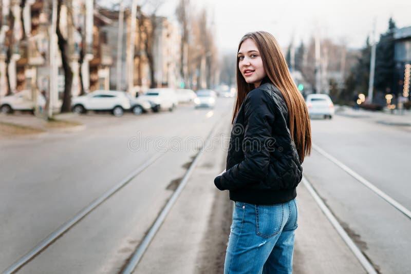 Portrait de dos de longs cheveux de fille élégante de mode marchant dessus sur le fond de ville Elle a la veste en cuir et les je images stock