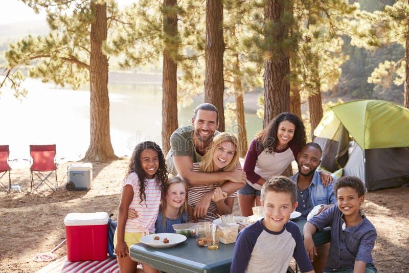 Portrait de famille avec des amis campant par le lac dans la forêt photo stock