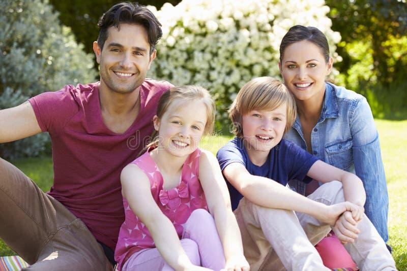 Portrait de famille détendant dans le jardin d'été photos stock