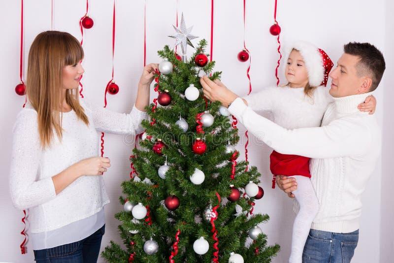 Portrait de famille heureuse décorant l'arbre de Noël photo libre de droits