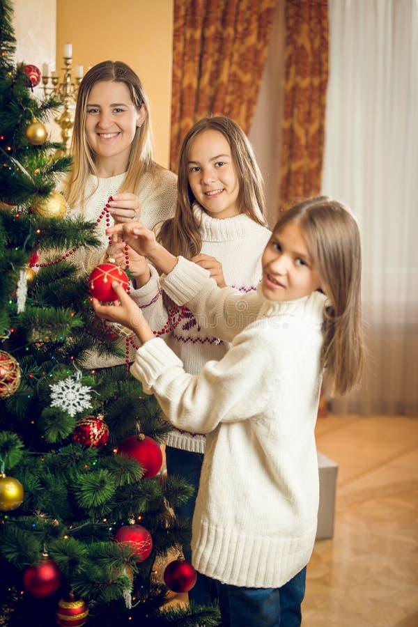 Portrait de famille heureuse décorant l'arbre de Noël au roo vivant images libres de droits