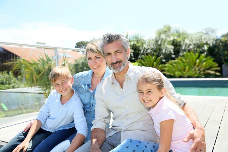 Portrait de famille heureuse devant la piscine photos stock