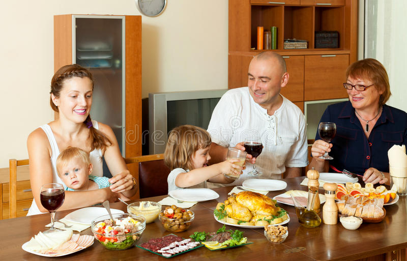 Portrait de famille heureuse ensemble au-dessus de la table de salle à manger mangeant le poussin photos libres de droits