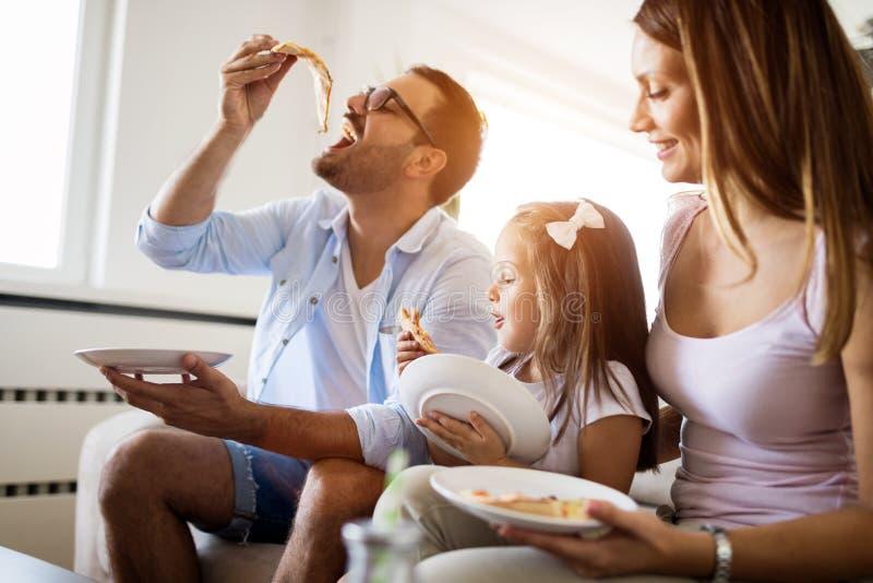 Portrait de famille heureuse partageant la pizza ? la maison photographie stock libre de droits