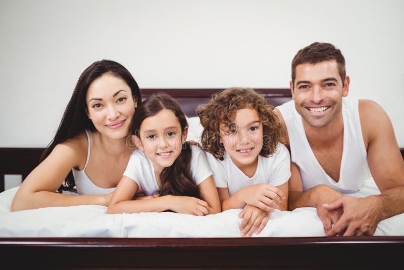 Portrait de famille heureuse se trouvant sur le lit à la maison photographie stock libre de droits