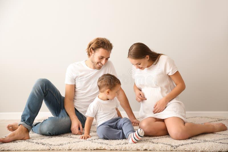 Portrait de famille heureuse sur le tapis près du mur blanc images stock
