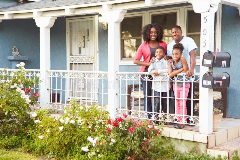Portrait de famille se tenant sur le porche de la maison suburbaine photos libres de droits