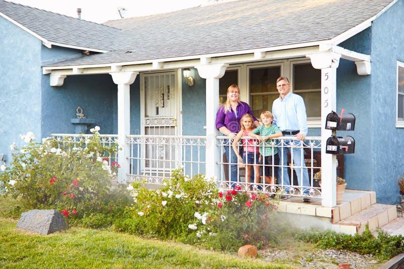 Portrait de famille se tenant sur le porche de la maison suburbaine photo stock