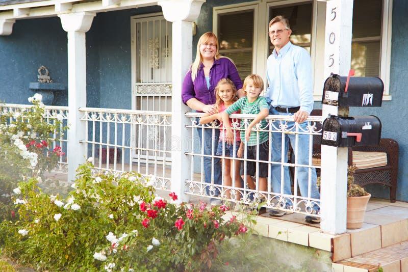 Portrait de famille se tenant sur le porche de la maison suburbaine photographie stock
