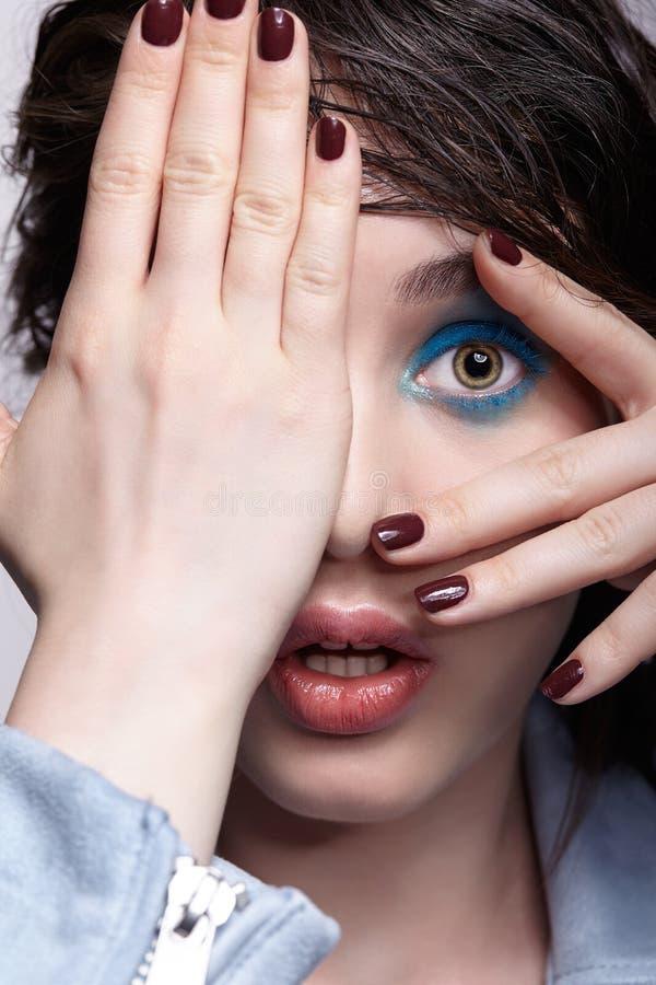 Portrait de femelle étonnée dans la veste bleue avec la main sur le visage Femme avec le maquillage peu commun de beauté et les c photo libre de droits