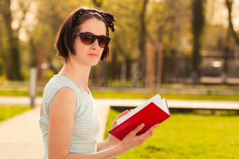 Portrait de femelle attirante lisant un livre en parc de ville photos stock