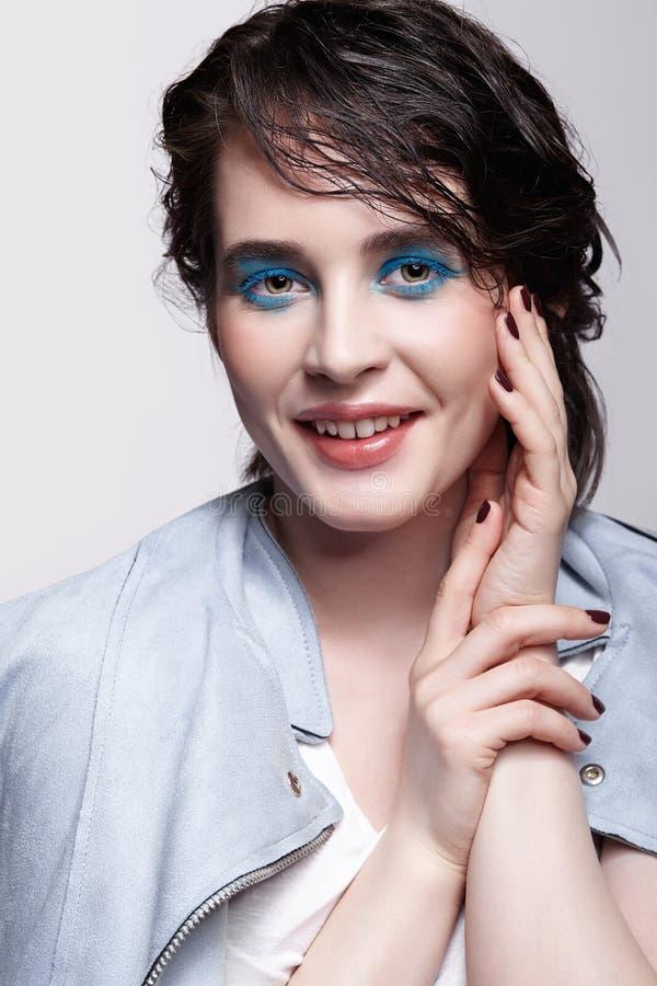 Portrait de femelle de sourire dans la veste bleue Femme avec le maquillage peu commun de beaut? et les cheveux humides, et maqui images libres de droits