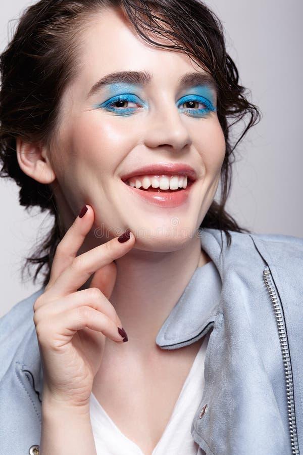 Portrait de femelle de sourire dans la veste bleue Femme avec le maquillage peu commun de beaut? et les cheveux humides, et maqui images stock