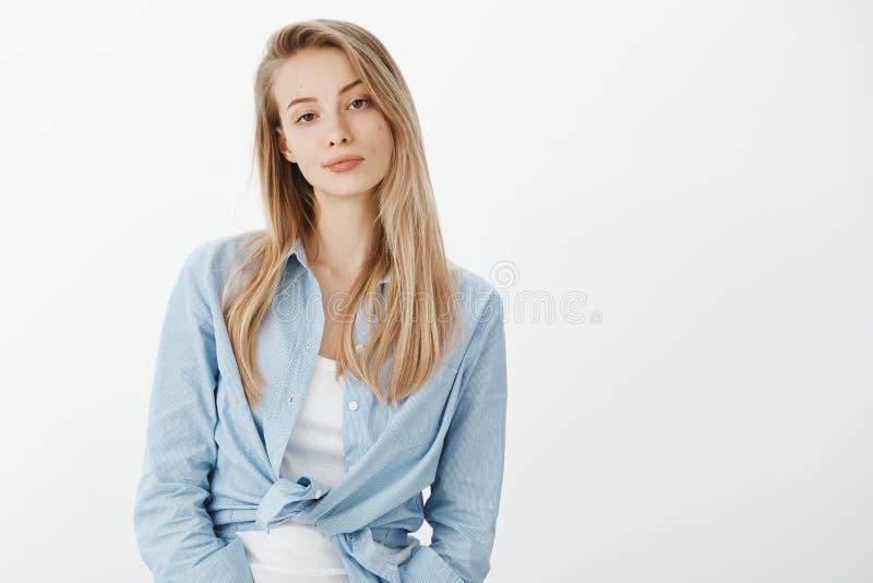 Portrait de femme élégante attirante détachée avec les cheveux blonds, souriant d'un air affecté et regardant indifférent l'appar photographie stock libre de droits