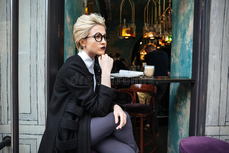 Portrait de femme élégante se reposant en seul café photographie stock