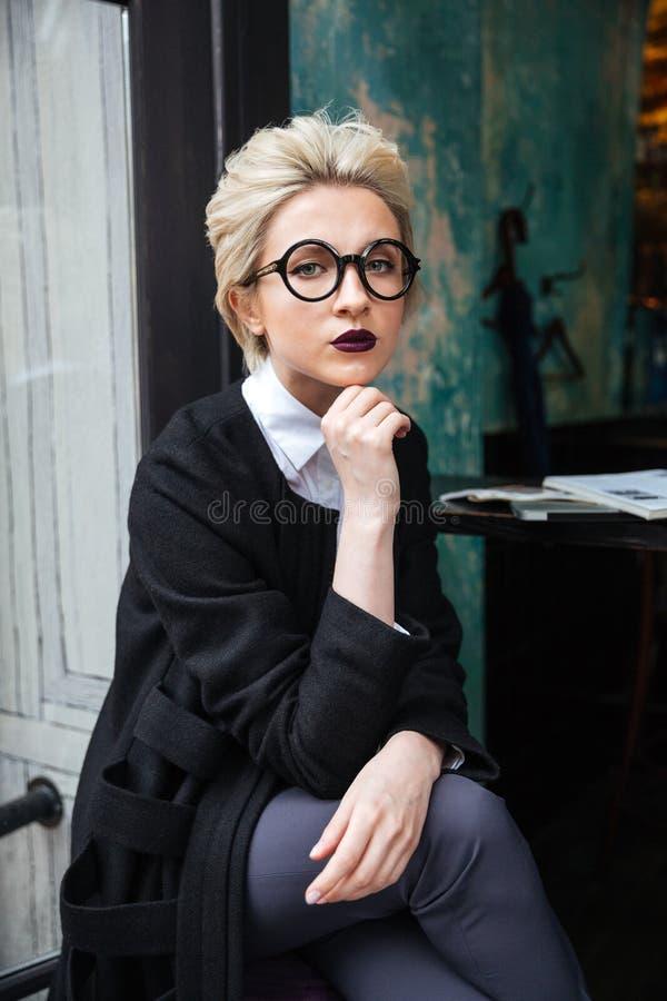 Portrait de femme élégante se reposant en seul café photos stock