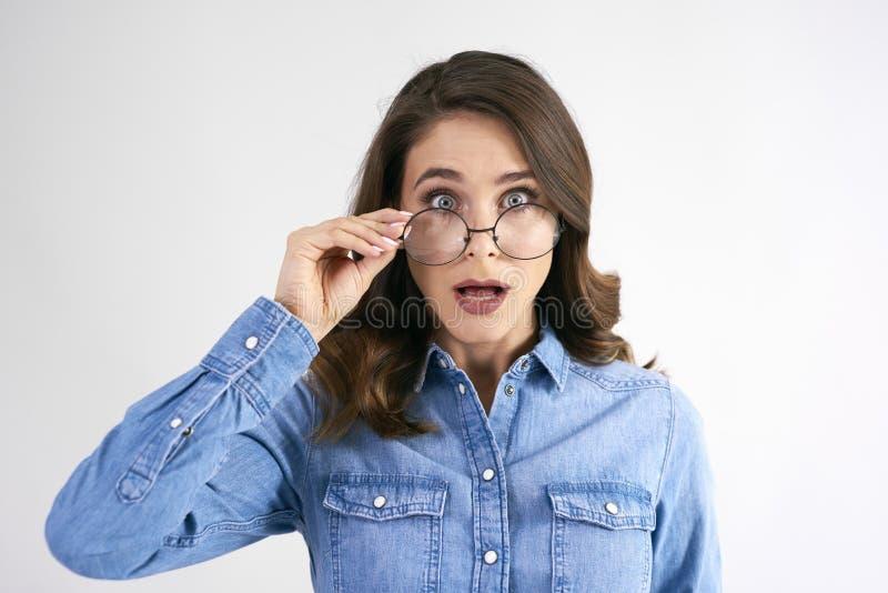 Portrait de femme étonnée avec des verres dans le tir de studio photos libres de droits