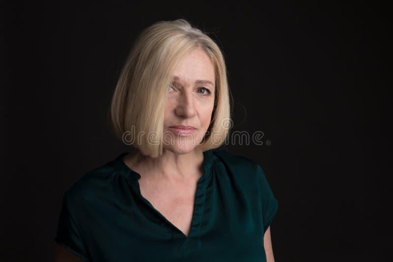 Portrait de femme adulte blonde d'isolement dans un studio sur un fond foncé photo stock