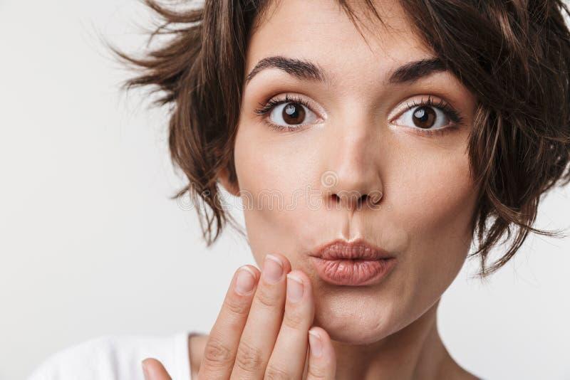 Portrait de femme affable avec les cheveux bruns courts dans le T-shirt de base couvrant sa bouche de main photographie stock libre de droits
