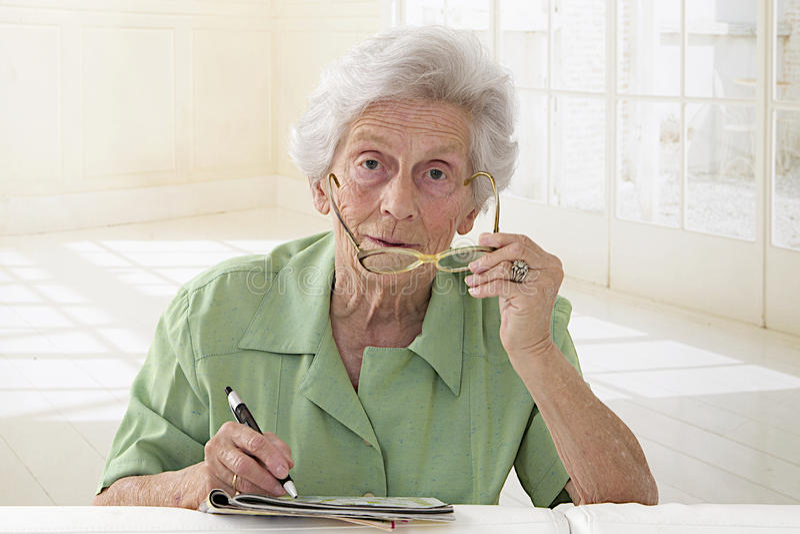 Portrait de femme agée tenant des verres et faisant des mots croisé photos stock