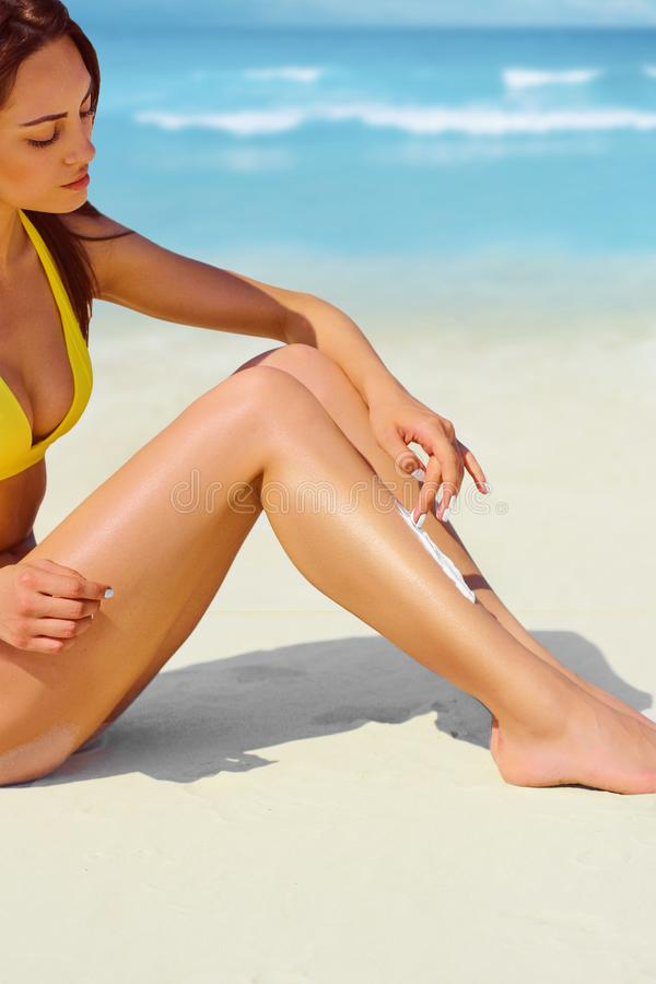 Portrait de femme appliquant la cr?me de protection du soleil ? la plage photos libres de droits