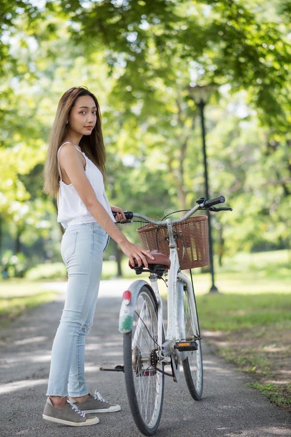 Portrait de femme asiatique avec le vélo en parc images stock