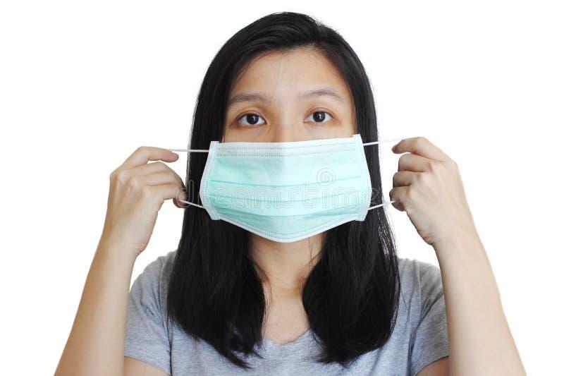 Portrait de femme asiatique mettant sur le masque médical sur le fond blanc photos stock