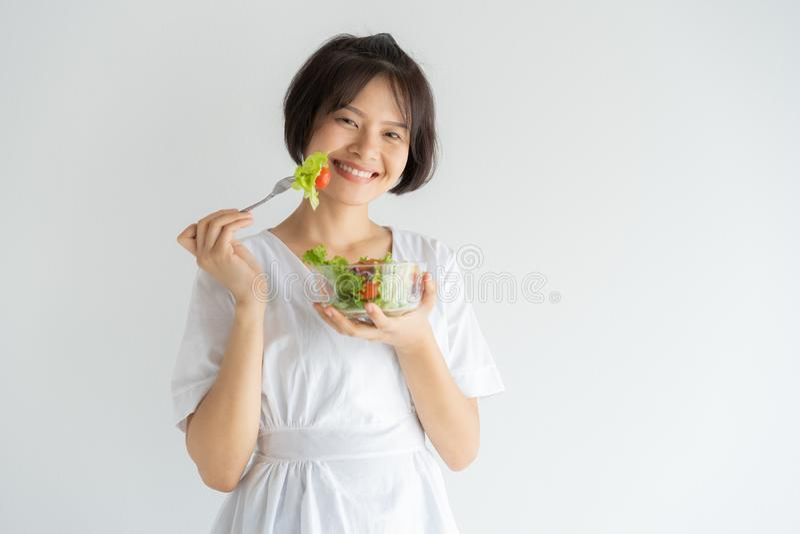 Portrait de femme asiatique souriant et mangeant de la salade sur le concept blanc de fond, sain et de mode de vie photos stock