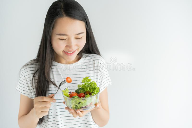 Portrait de femme asiatique souriant et mangeant de la salade sur le fond blanc à la maison, la nourriture pour des soins de sant image libre de droits