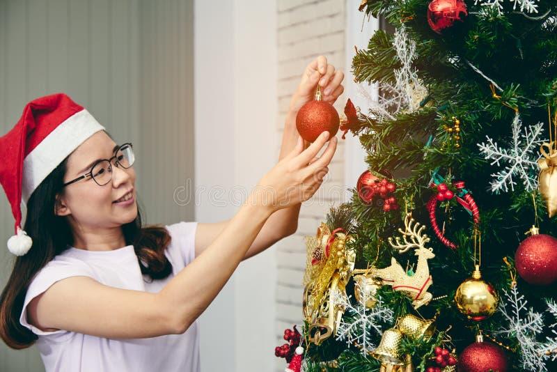 Portrait de femme asiatique utilisant le chapeau de Santa et décorant un arbre de Noël avec la boule rouge images stock