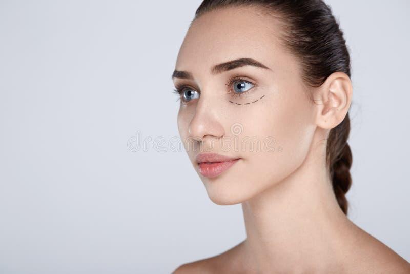 Portrait de femme attirante avec la ligne tirée de chirurgie plastique photo stock