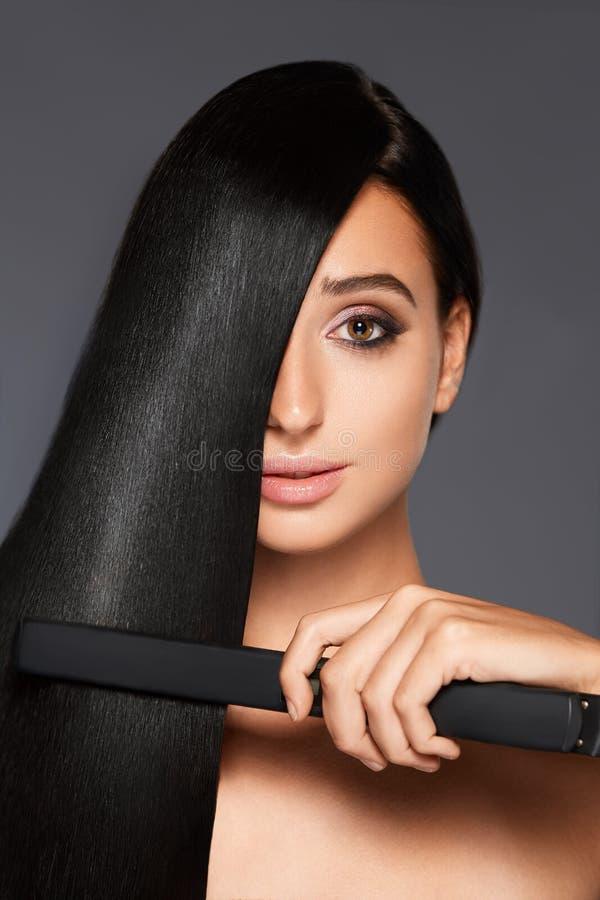 Portrait de femme attirante avec le redresseur de cheveux image stock
