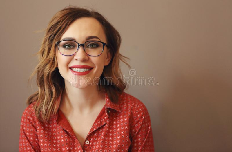 Portrait de femme attirante de brune avec des lunettes utilisant le chemisier rouge photographie stock
