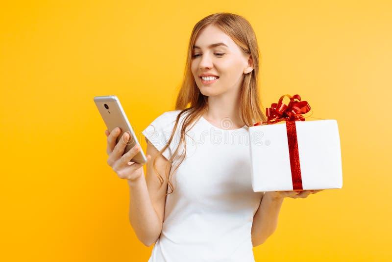 Portrait de femme attirante de sourire, boîte-cadeau de participation, tenant et à l'aide du téléphone portable, d'isolement sur  image stock