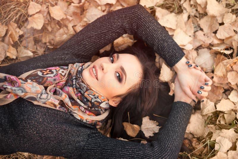 Portrait de femme au-dessus d'haut étroit de feuilles d'automne photo libre de droits