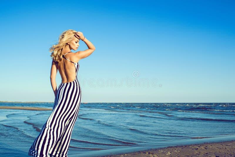 Portrait de femme aux cheveux longs blonde avec du charme dans la longue robe rayée noire et blanche avec la marche arrière nue l photo stock