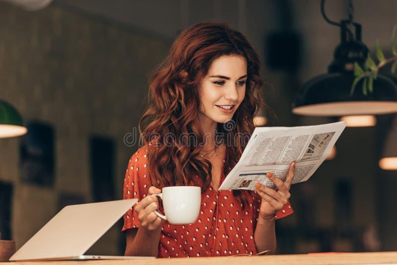 portrait de femme avec la tasse du journal de lecture de café à la table avec l'ordinateur portable photo libre de droits