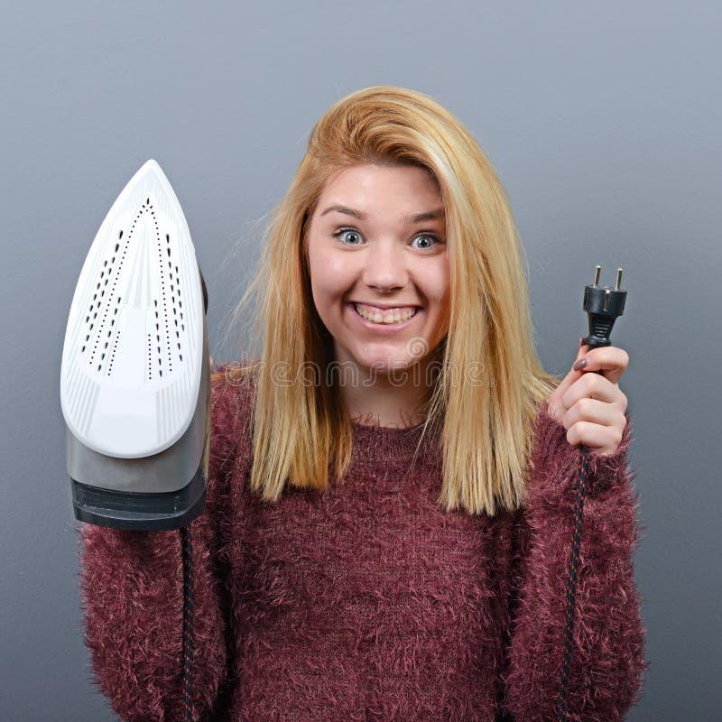 Portrait de femme avec le visage drôle tenant le fer sur le fond gris photo stock