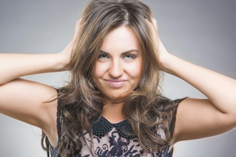 Portrait de femme avec les mains soulevées dans les cheveux photo stock