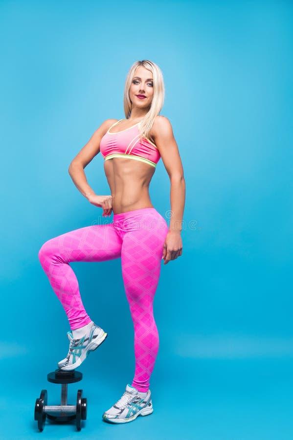 Portrait de femme blonde attirante dans les vêtements de sport roses posant avec des haltères sur le fond bleu photographie stock libre de droits