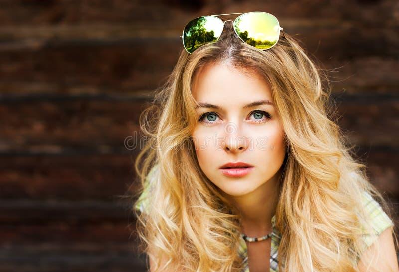 Portrait de femme blonde au mur en bois photo stock