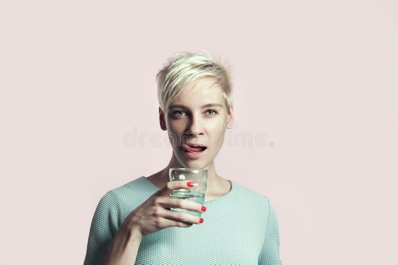 Portrait de femme blonde avec le verre de l'eau, fond lumineux de cheveux courts images stock
