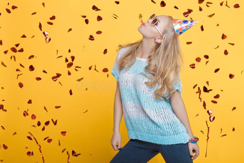 Portrait de femme blonde drôle dans le chapeau d'anniversaire et de confettis rouges sur le fond jaune Célébration et partie photos stock