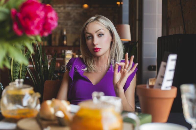 Portrait de femme blonde en café avec des fleurs images stock