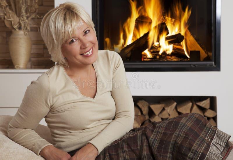 Portrait de femme blonde près de la cheminée à la maison images stock